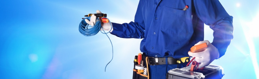 Electrician in blue overalls holding tools and wiring
