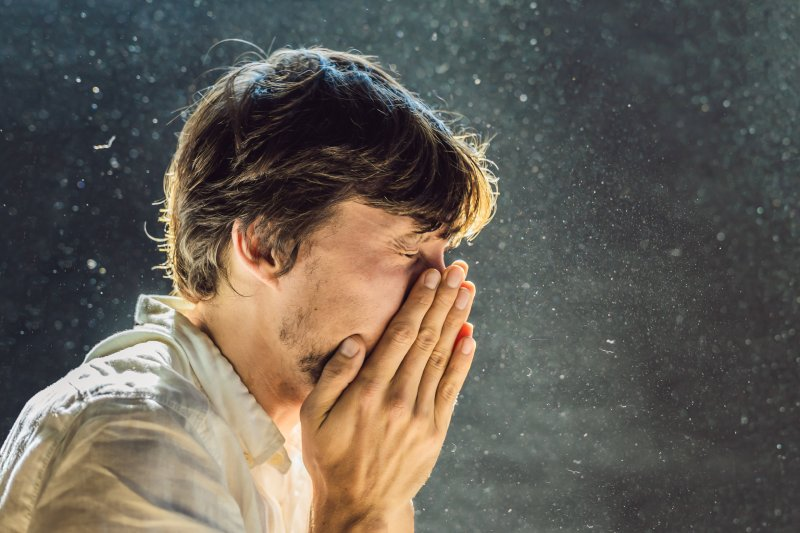 Man sneezing surrounded by dust in the air