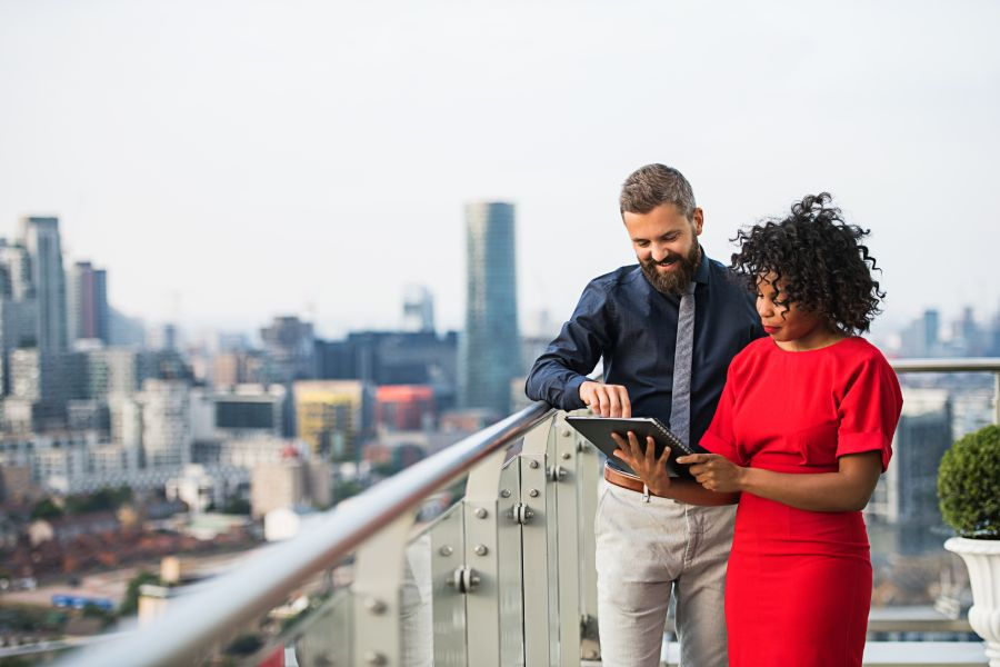 Man and woman looking at large notebook outside on a balcony