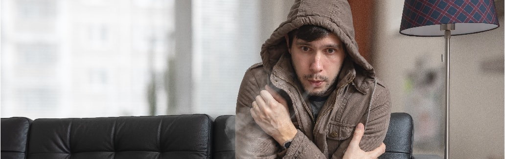 man sitting on sofa feeling cold