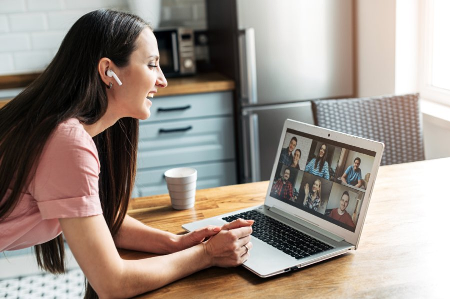 A lady taking part in an online meeting using a laptop