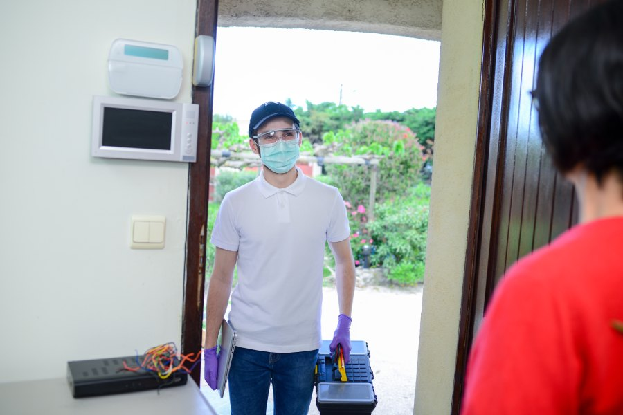Tradesperson wearing a mask at a front door of a home